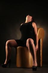 Frau sitzt breitbeinig im schwarzen Kleid