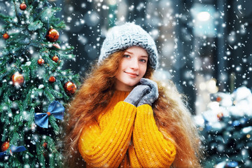 Young beautiful happy smiling redhead girl with freckles, long curly hair posing near Christmas tree, in street. Model wearing knitted beanie hat, yellow sweater. Snowfall. Winter holidays concept
