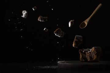 abstraktes Bild von explodierenden Brownies mit Blitzlicht auf schwarzem Hintergrund