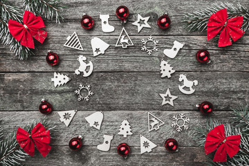 Four fir branches with red bows, and xmas handmade toys creating a circle on a wooden gray background, with space for text, Christmas greeting card