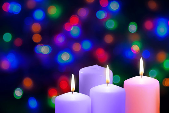 Christmas violet, purple and pink candles. Third Gaudete Sunday of the Advent. Shepherd Joy Candle. Xmas concept on a bokeh background.