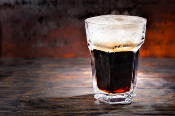 Big glass with freshly poured dark beer and head of foam on wooden desk