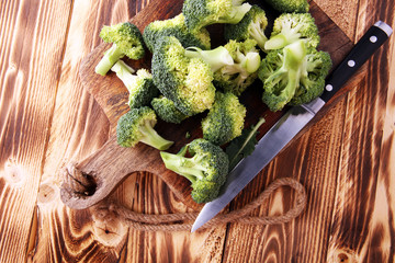 Fresh organic broccoli cut into small pieces on cutting board