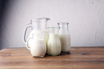 A jug of milk and glass of milk on a wooden table.