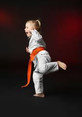Little girl practicing karate on dark background