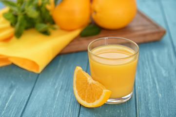 Glass of fresh orange juice on table