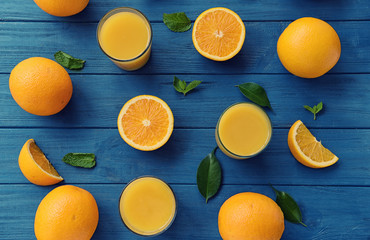 Composition with fresh oranges and glasses of juice on wooden background