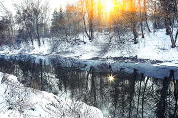 Winter landscape by a river in the sunset