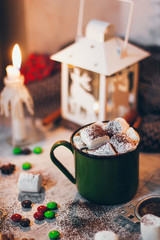 A coffee mug with cocoa on the Christmas lights and candles background with marshmallows