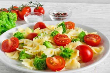 Broccoli farfalle pasta with tomato cherry in white plate on wooden table