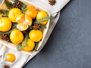 Fresh mandarins in a wooden basket with fir tree branches, star anise cinnamon on gray background Copy space