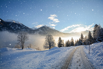 View to a icy road with snowfall and mountain range of Gasteinertal valley near Bad Gastein, Pongau austrian Alps - Salzburg Austria Europe