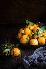 Tangerines with leaves on dark wooden table.