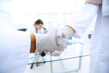 Doctors in lab coats greeting each other with handshake