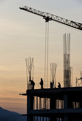 Silhouette of construction workers and building