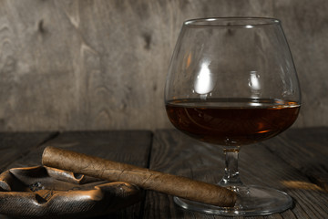 The cigar in the ashtray and a glass of cognac on oak textured table.