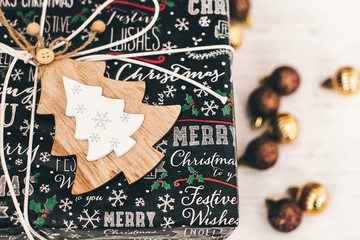 stylish wrapped gift box top view, with golden ornaments and tree. modern present. seasonal greetings, happy holidays. merry christmas and happy new year concept. space for text