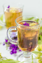 Linden herbal tea in a transparent grog glass with a linden blossom and bunch of herbs on the white wooden surface