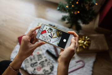 Concept of Christmas items. Woman's hands taking a photo.