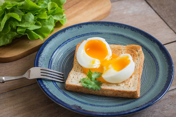 Soft boiled egg with toast on blue plate