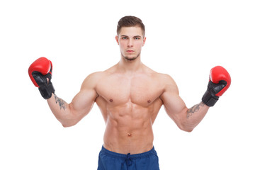 A boxer guy, with his naked torso and boxing gloves, stands with his arms raised at the shoulder level. Isolation.