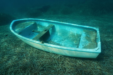 Underwater a small boat sunken on the seabed with leaves of Neptune grass, Mediterranean sea, Catalonia, Costa Brava, Spain