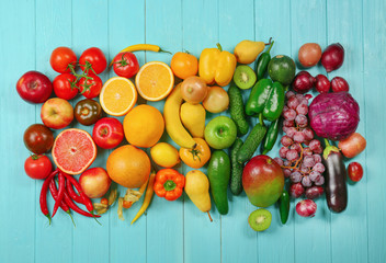 Creative composition made of fruits and vegetables in rainbow colors on wooden background, flat lay