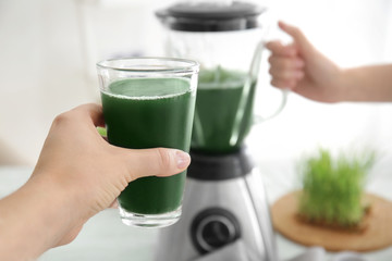 Woman with glass of wheat grass juice, close up