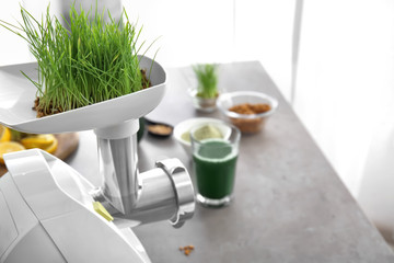 Making wheat grass juice on table in kitchen