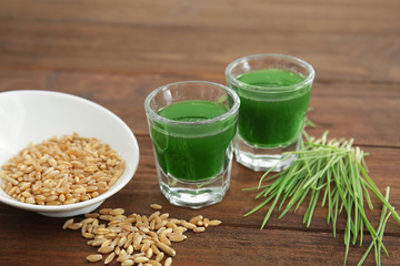 Shots of wheat grass juice and seeds on wooden table