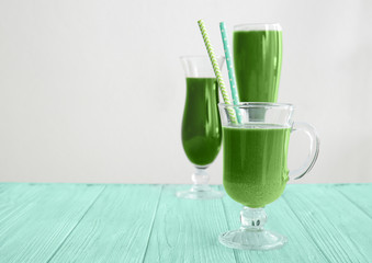 Glasses of wheat grass juice on white background