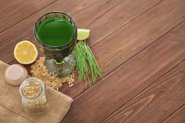 Glass of wheat grass juice and seeds on table