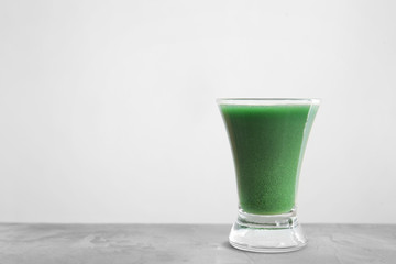 Shot of wheat grass juice on white background