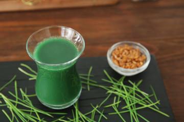 Shot of wheat grass juice on wooden board