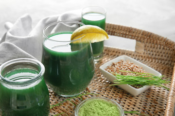 Glasses of wheat grass juice on wicker tray