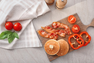 Tasty breakfast with pancakes, bacon and vegetables on wooden board