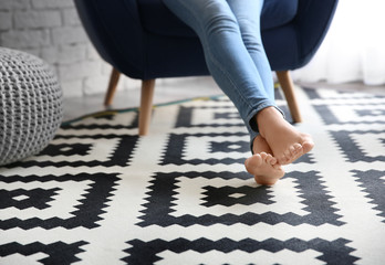 Woman sitting in armchair with feet on carpet at home
