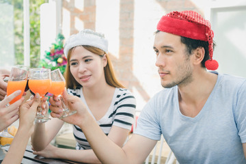 Group young people having drink and fun in santa hats throwing colorful on celebrating new year or christmas party, exchanging presents