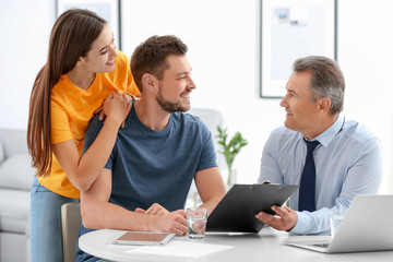Male insurance agent consulting young couple in office