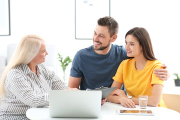 Female insurance agent consulting young couple in office