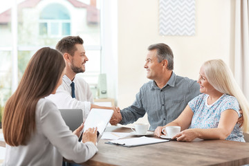 Insurance agents consulting senior couple in office