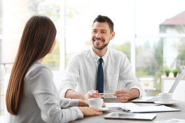 Insurance agent consulting young woman in office