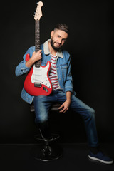 Young handsome musician with guitar on black background