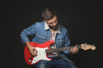 Young handsome musician playing guitar on black background
