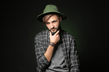 Thoughtful young hipster man on dark background
