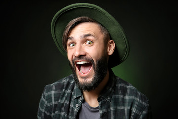 Excited young hipster man on dark background