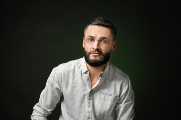 Portrait of handsome young hipster man on dark background