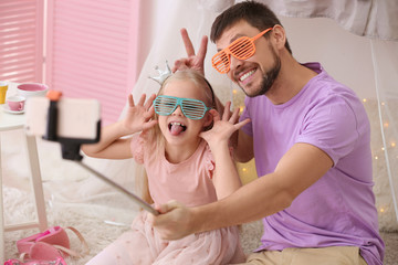 Father and his little daughter taking funny selfie at home