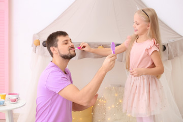 Cute little girl painting lips of her father at home