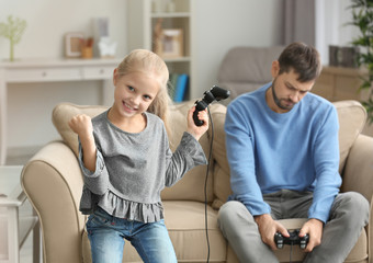 Happy little girl after winning videogame and her upset father at home